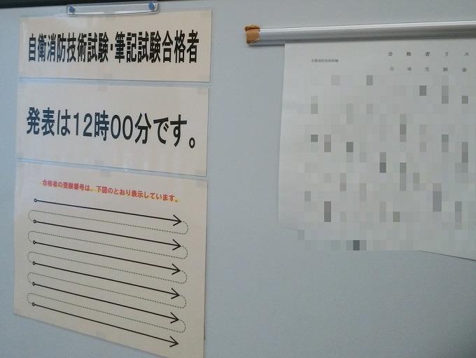 自衛消防技術認定試験の筆記試験の合格発表。建物入口のホワイトボードに合格者一覧が貼られる。